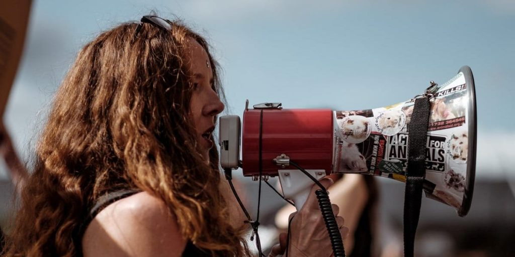 A female holding a loudspeaker during one of a protest march.