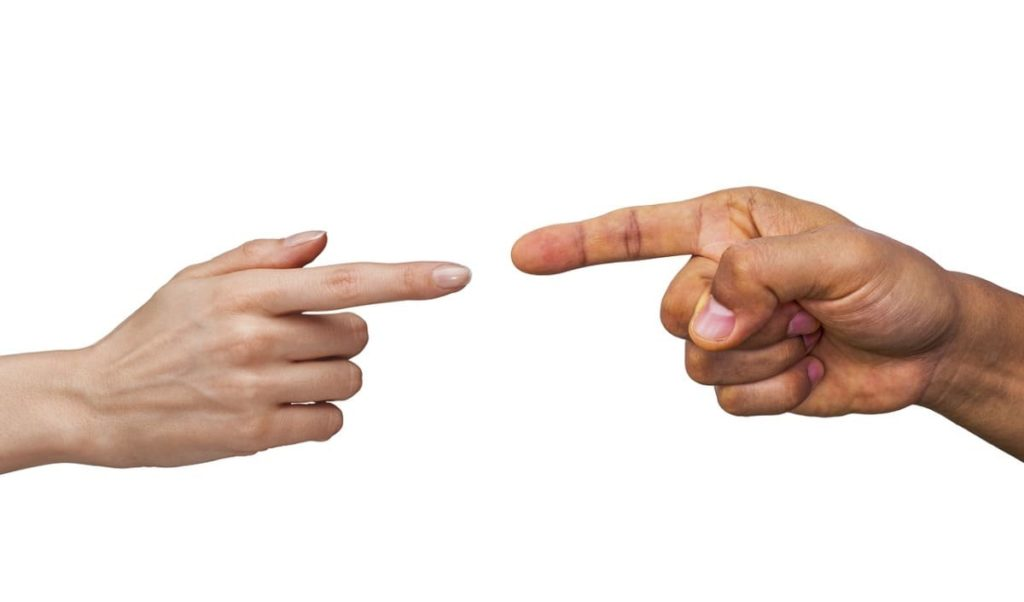 a female and a male index finger pointing at one another