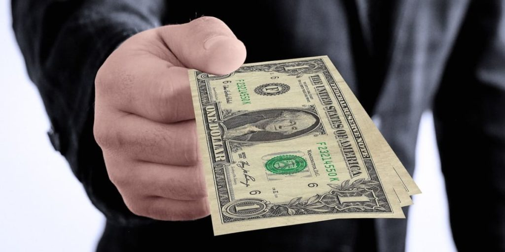 a man wearing a black suit is holding some dollars