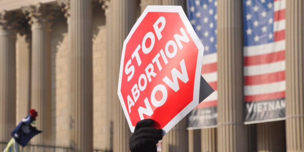 an anti abortion activist holding a placard
