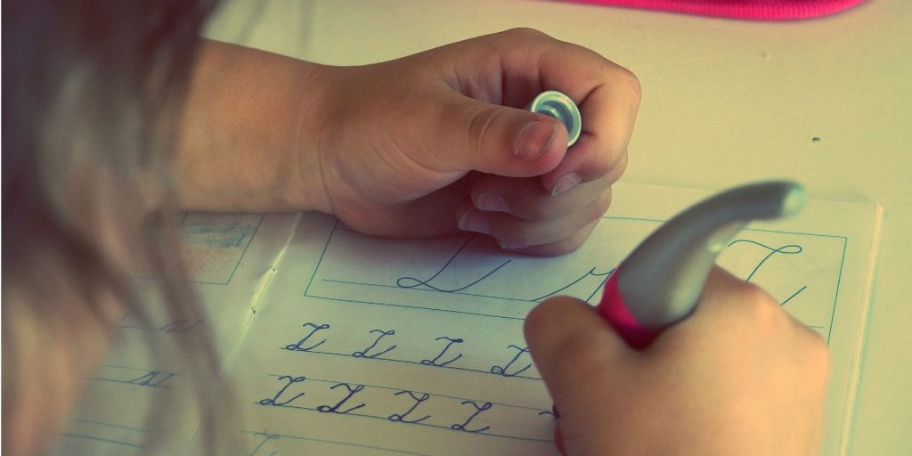 a girl is writing on her notebook