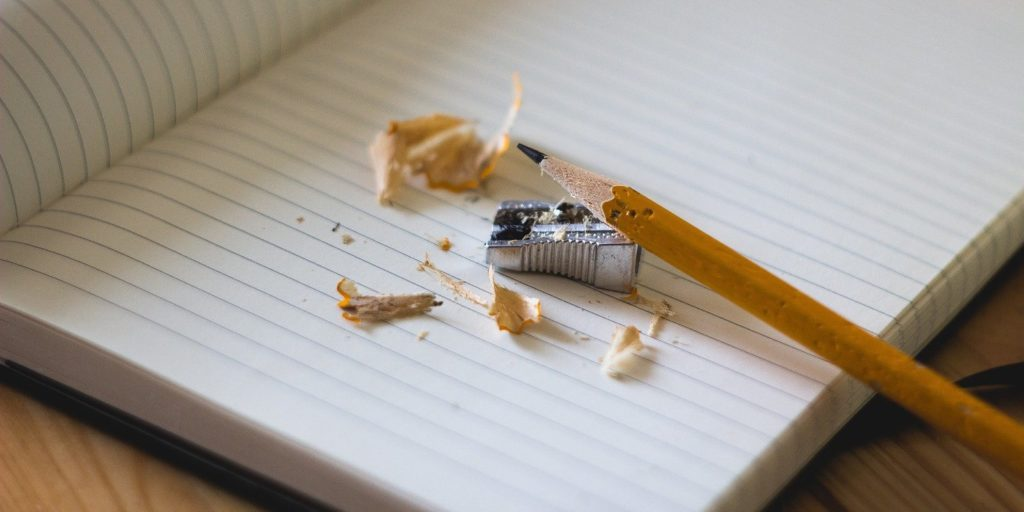 a pencil, a sharpener and a notebook