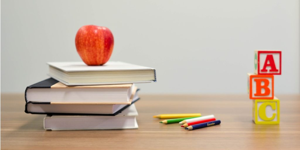 an apple on top of a stack of books, some color pencils and playing blocks